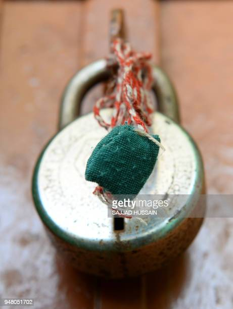 In this picture taken on April 17an amulet is seen hanging from a padlock at the house of the eightyearold girl who was raped and murdered at Rasana...