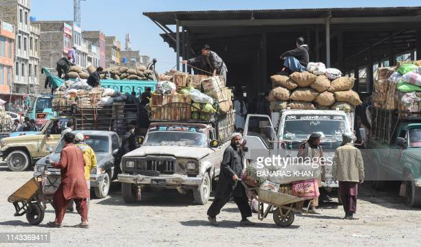 In this picture taken on April 18 Shiite Hazara minority traders load fruit and vegetables at a market before returning to their heavily guarded...