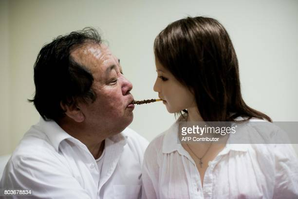 In this picture taken on April 20 62yearold Senji Nakajima shares a chocolate stick with his silicone sex doll Saori in bed at his apartment on the...
