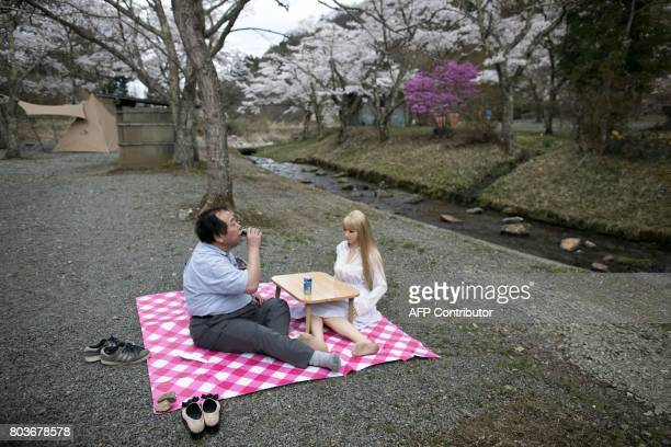 TOPSHOT In this picture taken on April 21 62yearold Senji Nakajima picnics with his silicone sex doll Saori under cherry blossoms in Yamanashi...