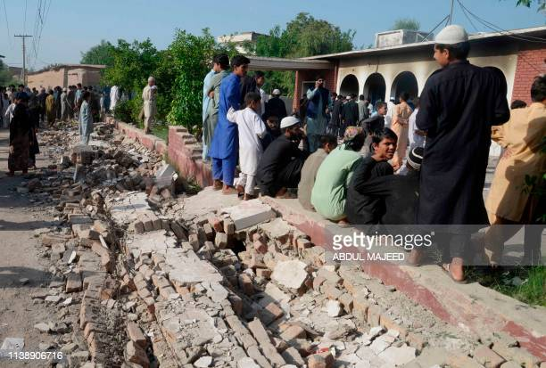 In this picture taken on April 22 Pakistani local residents gather outside a health centre torched by a mob following rumours of reactions by polio...