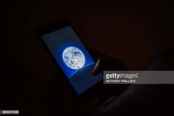 In this picture taken on April 24 24yearold Nicole a pseudonym she chose to protect her identity looks at a phone displaying the opening graphic for...