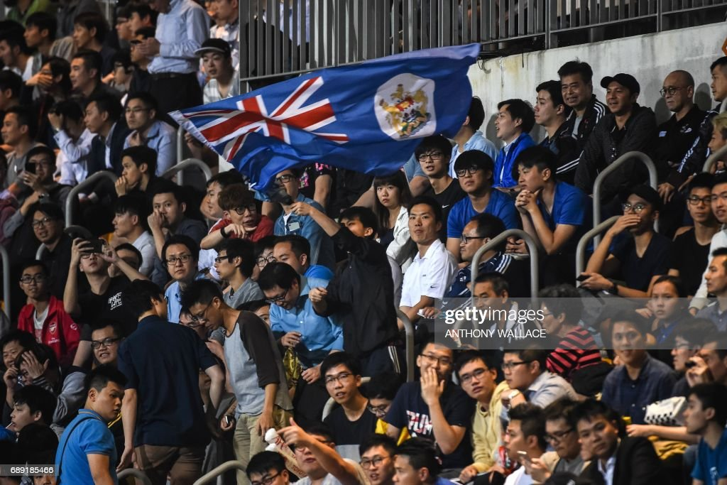 In this picture taken on April 25, 2017, a fan (C) of Hong Kong's Eastern waves the old British colonial flag of Hong Kong during the AFC Champions League football match between China's Guangzhou Evergrande and Hong Kong's Eastern at Mongkok Stadium in Hong Kong. From its rattling trams and racecourses to its legal system and the ubiquitous consumption of Spam, Britain's colonial legacy still resonates through Hong Kong. But almost 20 years since the city was handed back to China under a deal that made it semi-autonomous, colonial emblems have become a symbol of protest. / AFP PHOTO / Anthony WALLACE / TO GO WITH Hong Kong-China-Britain-politics-history-culture-handover, FEATURE by Laura MANNERING