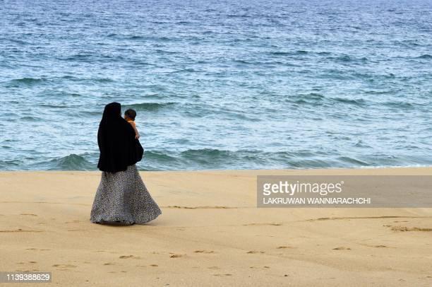 In this picture taken on April 25 a Sri Lankan Muslim woman walks along a beach with her child in Kattankudy Zahran Hashim's swordwielding zealotry...