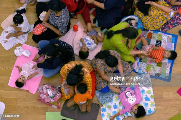 In this picture taken on April 28 Indian parents change diapers of their babies as part of an environmental event 'The Great Cloth Diaper Change' in...