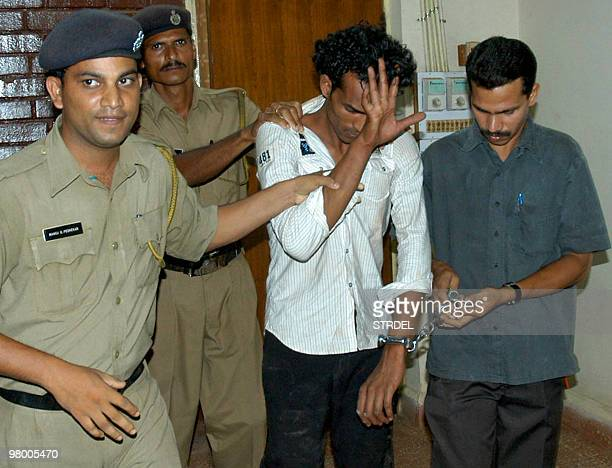In this picture taken on April 29 Indian police officials escort Anand Kamble after his arrest at a police station in Goa A beach bar waiter was...