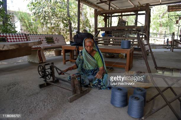 In this picture taken on April 4 Indian weaver Ramaben Badhia rolls thread to be used for hand weaving khadi denim jeans cloth at the Imam Manzil...