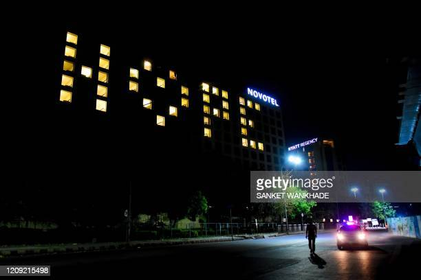 In this picture taken on April 5 2020 hotel rooms with its lights switchedon form the word Hope in the facade during a nineminute vigil in which...