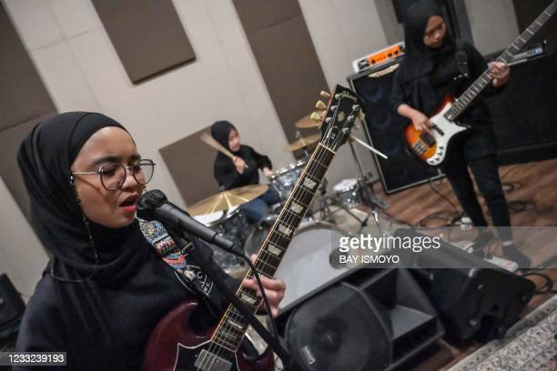 In this picture taken on April 8 members of the Indonesian heavy metal band Voice of Baceprot , guitarist and vocalist Firda Marsya Kurnia , drummer...