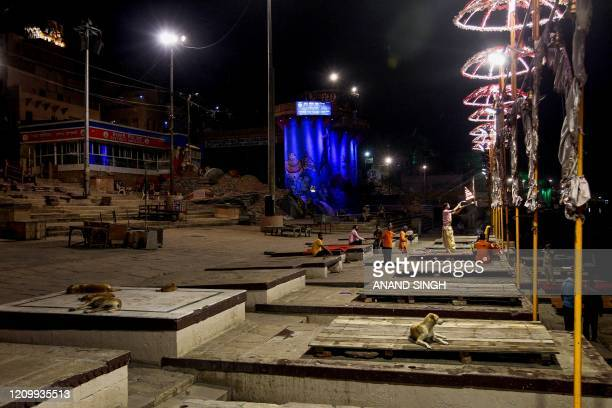 In this picture taken on April 9 2020 a lone Hindu priest performs an evening prayer at the Dashashwamedh Ghat on the banks of the Ganges river...