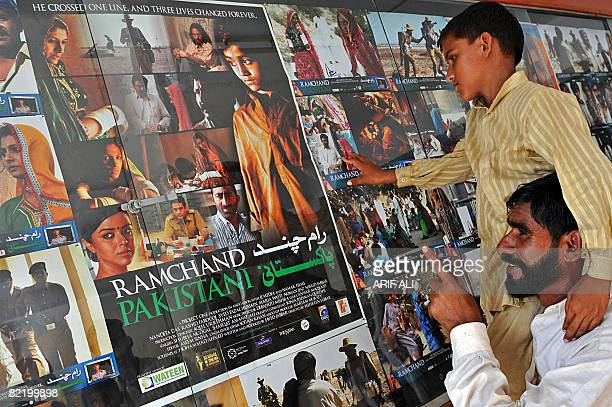 In this picture taken on August 1, 2008 a Pakistani man carries his son on his shoulder as they look at the poster of the India and Pakistan...