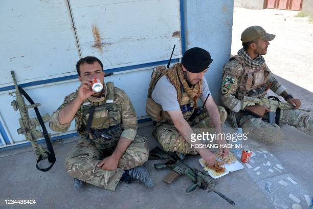 In this picture taken on August 1 Afghan National Army commando forces rest as they eat their lunch along a road amid ongoing fighting between...