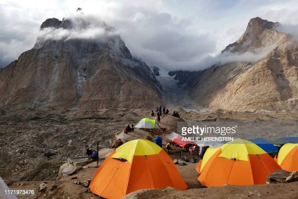 In this picture taken on August 10, 2019 foreign tourists and porters rest at a camping site above Baltoro glacier in the Karakoram range of...