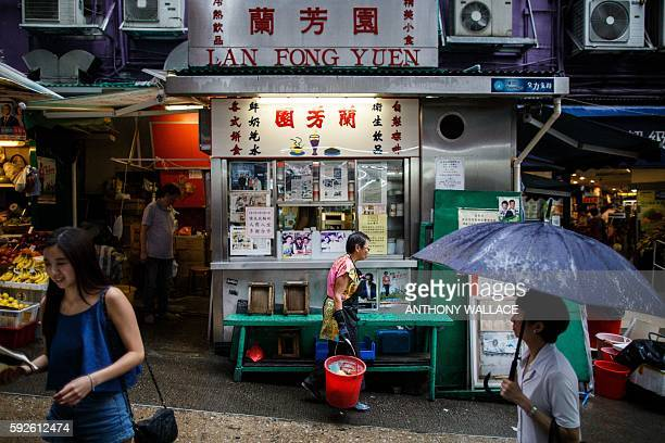 In this picture taken on August 10 pedestrians walk past family-run teashop Lan Fong Yuen , on a hilly market street in Hong Kong's Central...