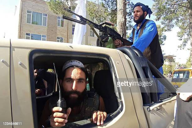 In this picture taken on August 13 Taliban fighters are pictured in a vehicle along the roadside in Herat, Afghanistan's third biggest city, after...