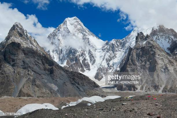 In this picture taken on August 14, 2019 foreign tourists and porters are seen at the Concordia camping site in the Karakoram range of Pakistan's...