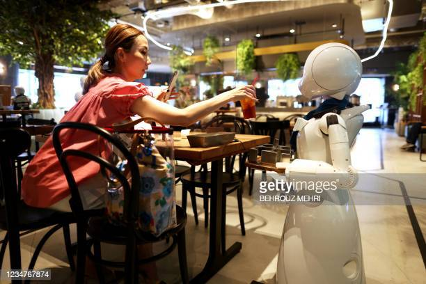 In this picture taken on August 17 a humanoid robot delivers drinks to customers at the Dawn Cafe in Tokyo. - The cafe's launch comes with the...
