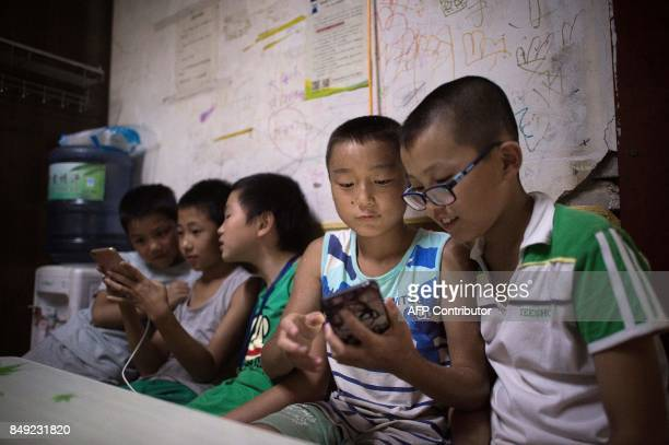 In this picture taken on August 17 children play smartphone games inside a room in a migrant village on the outskirts of Beijing Surrounded by the...