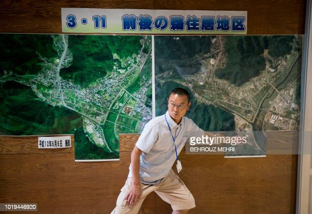 In this picture taken on August 18 2018 Kenji Sesake principal of KamaishiEast junior high school shows maps of Kamaishi area before and after the...