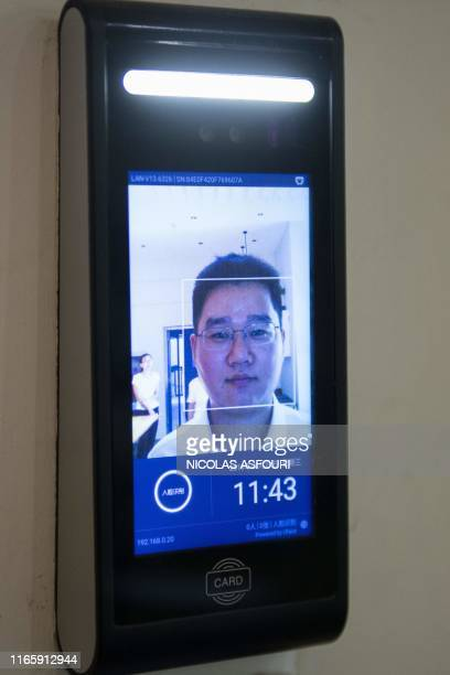 In this picture taken on August 21 2019 a man uses a facial recognition device installed at an IFuree Go selfservice supermarket in Tianjin China's...