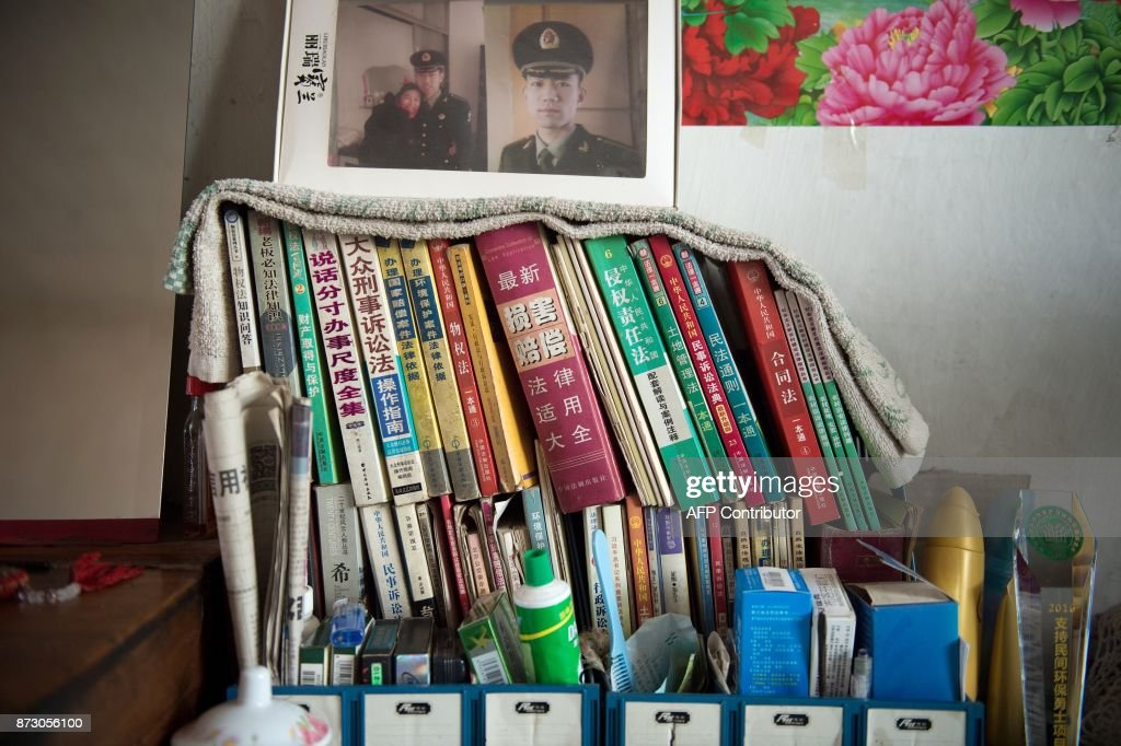 In this picture taken on August 21, 2017, books are stacked inside the room of farmer Wang Enlin in his house in Yushutun. Wang Enlin, an elderly farmer who left school when he was 10 years old and taught himself law armed with a single textbook and dictionary, makes for an unlikely eco-warrior. Yet the 64-year-old is determined to reap justice as he readies for a fresh battle in his war with a subsidiary of China's largest chemical firm, which he accuses of polluting and destroying his farmland. / AFP PHOTO / Nicolas ASFOURI / TO GO WITH China-justice-environment, FEATURE by Yanan WANG