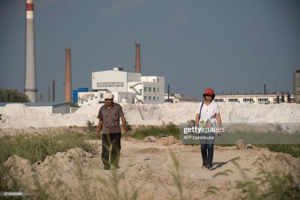 In this picture taken on August 21, 2017, farmer Wang Baoqin (R) and a fellow member (L) of 'Senior Citizen Environmental Protection Team' walk on the villager farmland that was polluted by the Qihua chemical plant (back) in Yushutun. Wang Enlin, an elderly farmer who left school when he was 10 years old and taught himself law armed with a single textbook and dictionary, makes for an unlikely eco-warrior. Yet the 64-year-old is determined to reap justice as he readies for a fresh battle in his war with a subsidiary of China's largest chemical firm, which he accuses of polluting and destroying his farmland. / AFP PHOTO / Nicolas ASFOURI / TO GO WITH China-justice-environment, FEATURE by Yanan WANG