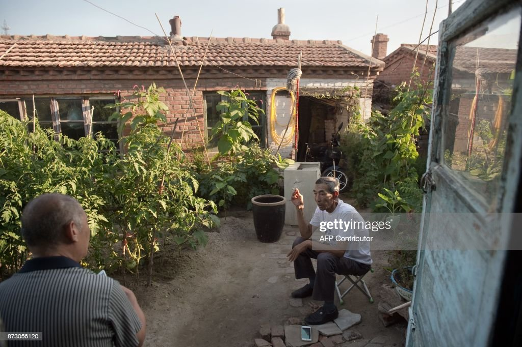 In this picture taken on August 21, 2017, farmer Wang Enlin (R) sits in his garden at his house in Yushutun. Wang Enlin, an elderly farmer who left school when he was 10 years old and taught himself law armed with a single textbook and dictionary, makes for an unlikely eco-warrior. Yet the 64-year-old is determined to reap justice as he readies for a fresh battle in his war with a subsidiary of China's largest chemical firm, which he accuses of polluting and destroying his farmland. / AFP PHOTO / Nicolas ASFOURI / TO GO WITH China-justice-environment, FEATURE by Yanan WANG