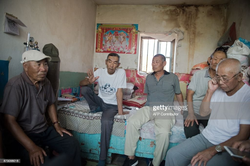 In this picture taken on August 21, 2017, farmer Wang Enlin (2nd L) sits in his room with his 'Senior Citizen Environmental Protection Team' inside his house in Yushutun. Wang Enlin, an elderly farmer who left school when he was 10 years old and taught himself law armed with a single textbook and dictionary, makes for an unlikely eco-warrior. Yet the 64-year-old is determined to reap justice as he readies for a fresh battle in his war with a subsidiary of China's largest chemical firm, which he accuses of polluting and destroying his farmland. / AFP PHOTO / Nicolas ASFOURI / TO GO WITH China-justice-environment, FEATURE by Yanan WANG