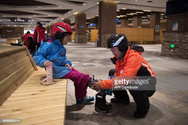 In this picture taken on August 22 a man helps a girl to wear ski boots at the Wanda Harbin Ice and Snow Park in Harbin At Dalian Wanda Group's new...