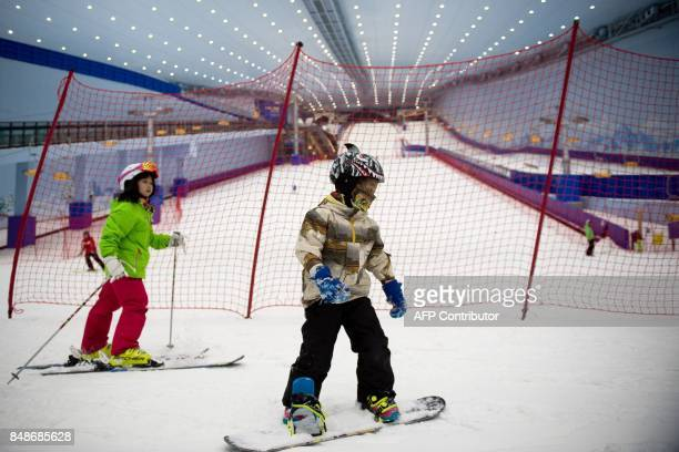 In this picture taken on August 22 children snowboard and surf at the Wanda Harbin Ice and Snow Park in Harbin At Dalian Wanda Group's new Ice and...