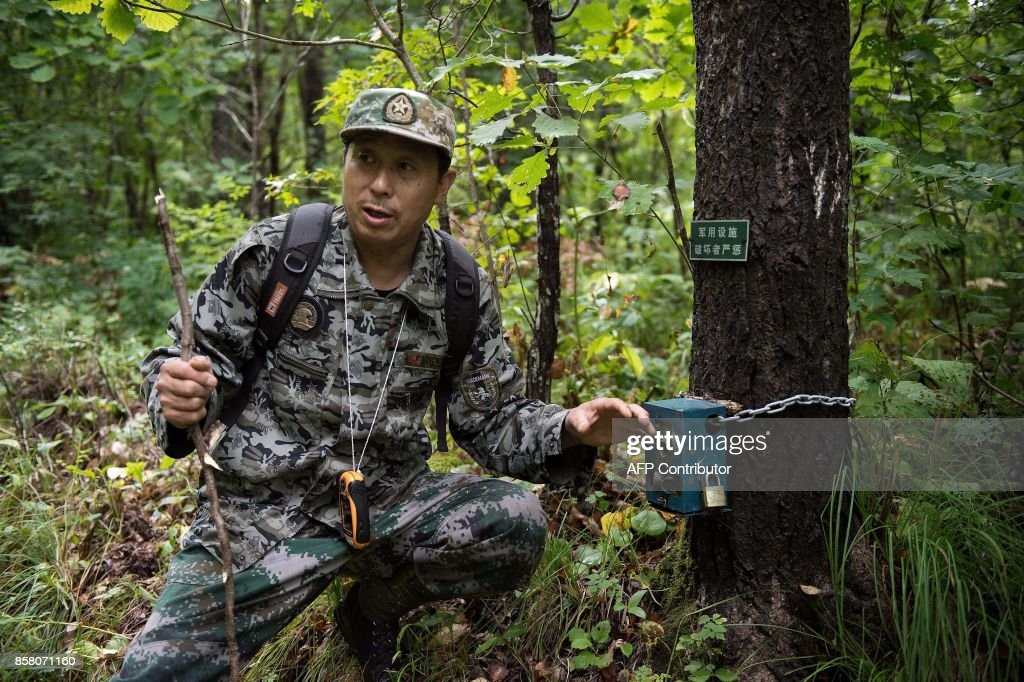 In this picture taken on August 24, 2017, Liang Fengen, a ranger at the Nuanquan River Forestry Centre, shows a heat sensor camera as he surveys an area in Suiyang town, Mudanjiang municipality. In the northern mountains bordering Russia, everyone knew the spry Chinese man as a skilled and ruthless hunter -- the kind who once killed a mother black bear as her cubs looked on. But instead of stalking the woods for prey, Liang Fengen now roams the hills without a rifle, working as a ranger to save the area's endangered Siberian tiger population and protect other wildlife. / AFP PHOTO / Nicolas ASFOURI / TO GO WITH China-conservation-animal, FEATURE by Yanan WANG