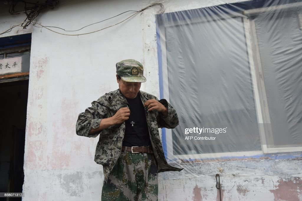 In this picture taken on August 24, 2017, Liang Fengen, a ranger at the Nuanquan River Forestry Centre, gets ready to survey an area in Suiyang town, Mudanjiang municipality. In the northern mounta...