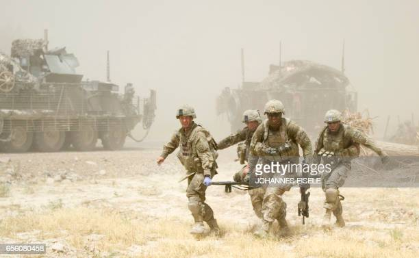 In this picture taken on August 25 2011 US soldiers carry a wounded soldier to the Medevac of 159th Brigade Task Force Thunder helicopter to be...
