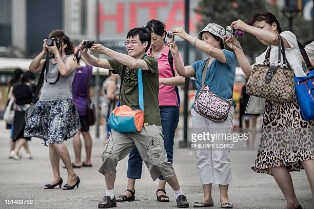 In this picture taken on August 28 tourists from mainland China take pictures during a visit to Hong Kong Hong Kong said on September 7 2012 that...
