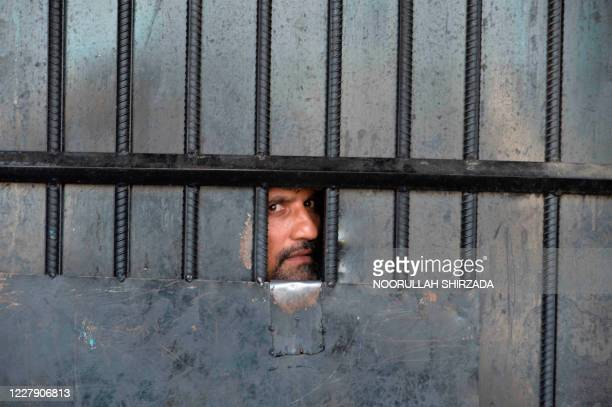 In this picture taken on August 3 an inmate watches from behind a closed gate after a raid at the prison in Jalalabad. - At least 29 people were...