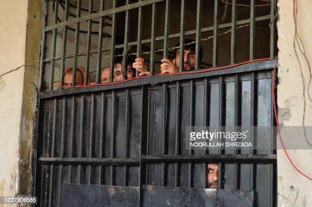 In this picture taken on August 3 inmates watch from behind a closed gate after a raid at the prison in Jalalabad. - At least 29 people were killed...