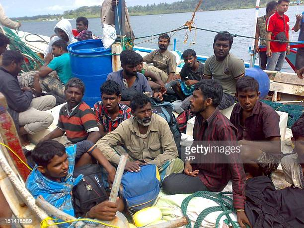 In this picture taken on August 30 2012 Sri Lankan asylumseekers sit on their boat in the Mentawai island group in West Sumatra More than 50...