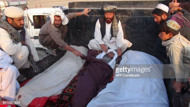 In this picture taken on August 30 2017 Afghan men sit next to dead bodies of those allegedly killed in a US air strike in DashteBari village in...
