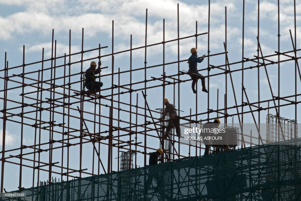 In this picture taken on August 30, 2018, workers are seen on a scaffold close to the terminal building of the new Beijing Daxing international airport under construction in Beijing.