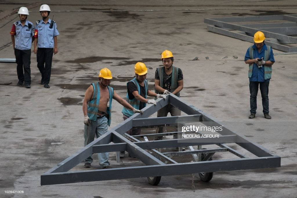 In this picture taken on August 30, 2018, workers push a steel structure inside the terminal building of the new Beijing Daxing international airport under construction in Beijing.