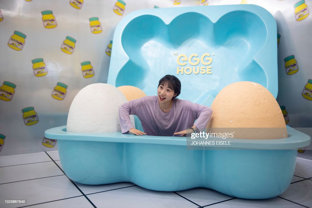 In this picture taken on August 31, 2018, a visitor poses for a photograph at the Egg House in Shanghai. - 'The Egg House' in Shanghai is where an apparently unhealthy interest in eggs and selfies meets Alice in Wonderland. Generously described as 'an egg-themed pop-up exhibition' in Chinese state media, the installation is unashamedly all about one thing -- photos and selfies.