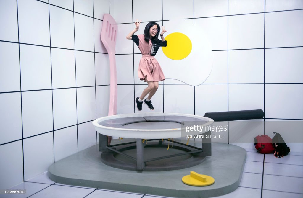 In this picture taken on August 31, 2018, a visitor poses for a photograph on a trampoline guised as a giant egg frying pan at the Egg House in Shanghai. - 'The Egg House' in Shanghai is where an apparently unhealthy interest in eggs and selfies meets Alice in Wonderland. Generously described as 'an egg-themed pop-up exhibition' in Chinese state media, the installation is unashamedly all about one thing -- photos and selfies.