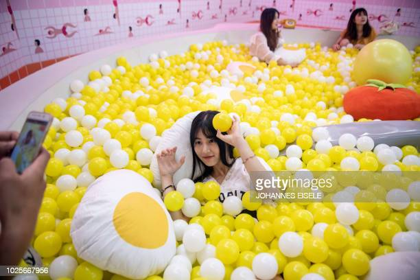 In this picture taken on August 31 a visitor poses for a photograph inside a giant caviar bowl at the Egg House in Shanghai 'The Egg House' in...