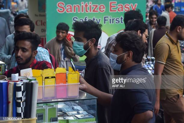 In this picture taken on August 31 men wearing facemasks as a preventive measure against the Covid-19 coronavirus visit a mobile phone market in...