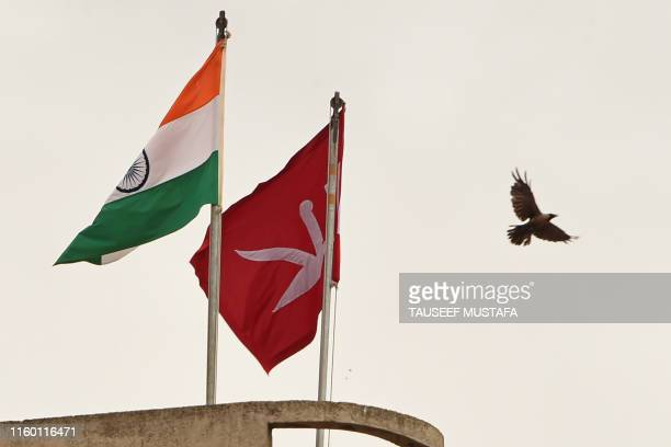 In this picture taken on August 6 2019 an Indian national flag flies next to a Jammu and Kashmiri flag ontop of civil secretariat building during a...