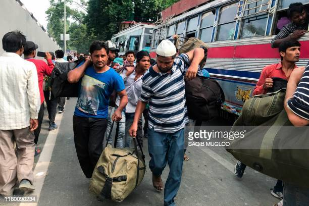 In this picture taken on August 6 2019 people arrive with their bags at the tourist centre to board buses to leave from Srinagar Kashmir was stripped...