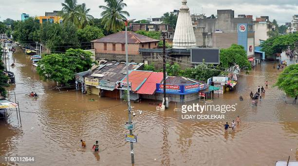 In this picture taken on August 6, 2019 people wade through a flood street in Sangli, Maharashtra.