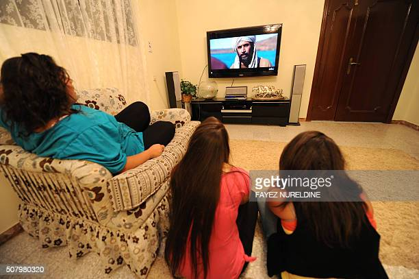 In this picture taken on August 6 Saudi sisters Aseel Saraa and her friend Saudi Sama watch the Islamic series 'Omar' on TV at their home in Malaz...