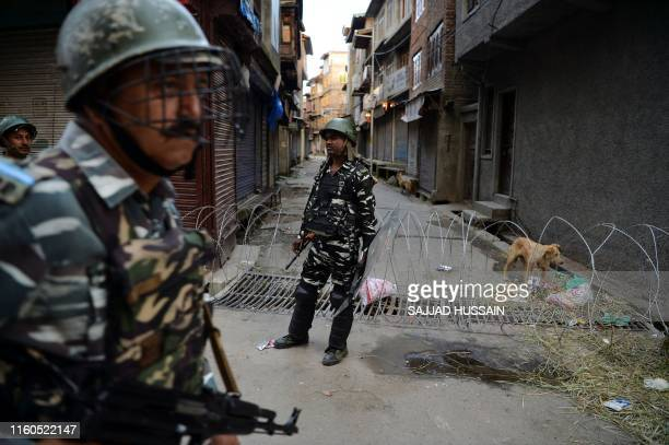 In this picture taken on August 9 2019 security personnel stand guard on a street in downtown Srinagar as widespread restrictions on movement and a...