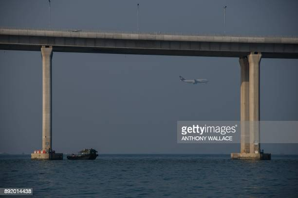 In this picture taken on December 11 a boat transporting construction workers berths next to a column of the Hong KongZhuhaiMacau Bridge as a plane...